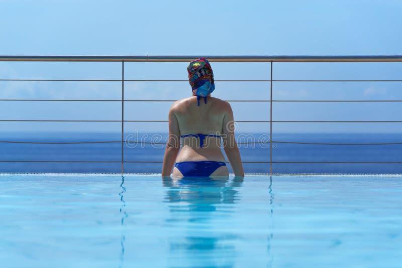 Mujer joven en la piscina del infinito imagenes de archivo