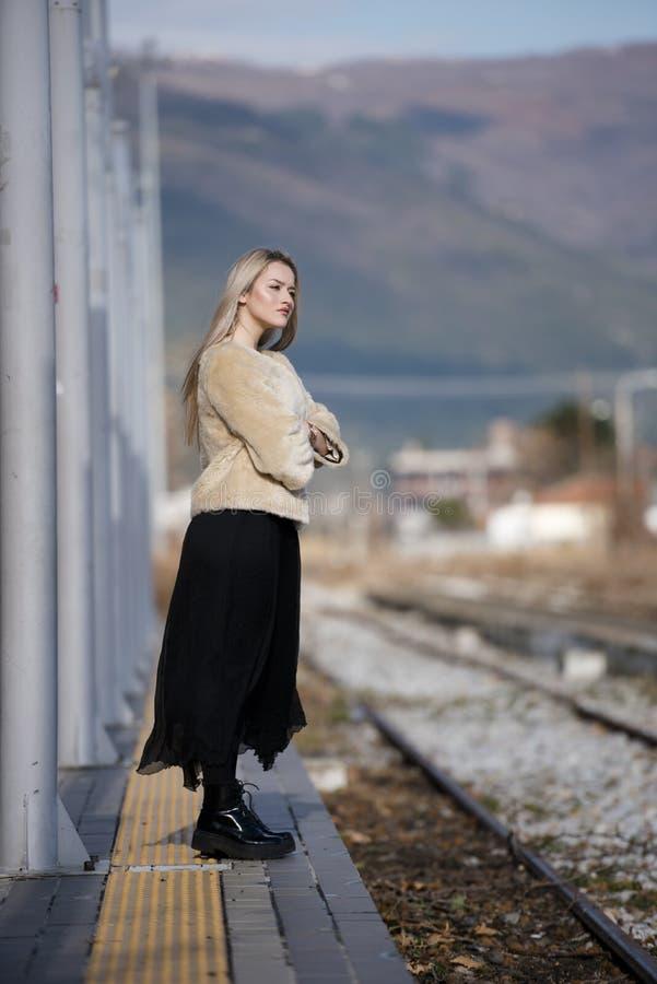 Mujer joven en la plataforma del ferrocarril del borde fotografía de archivo