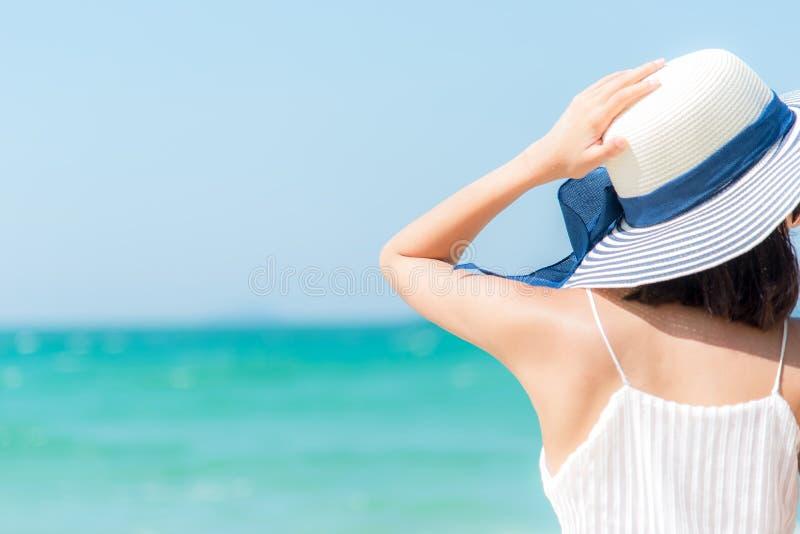Mujer joven en la playa de la isla de Formentera Feliz y relaje la mano de la mujer que sostiene el sombrero grande en la playa b fotografía de archivo libre de regalías
