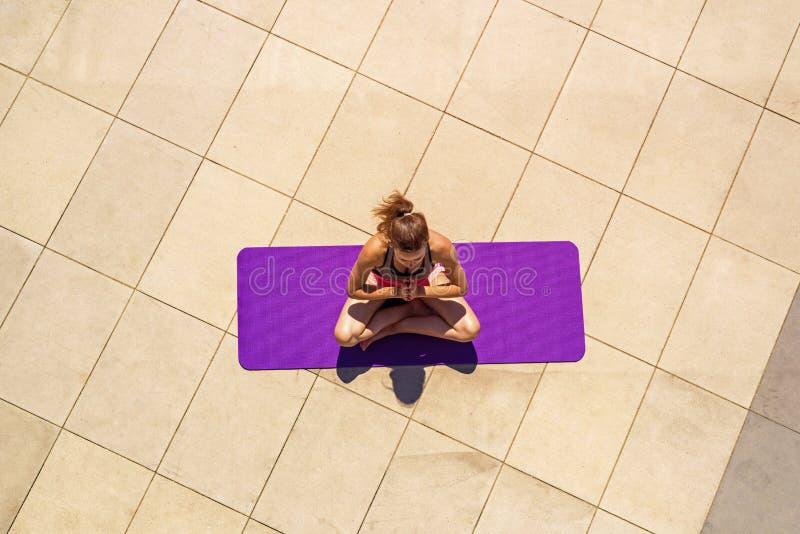 Mujer joven en la posición de loto en el día soleado, al aire libre, visión desde a fotografía de archivo