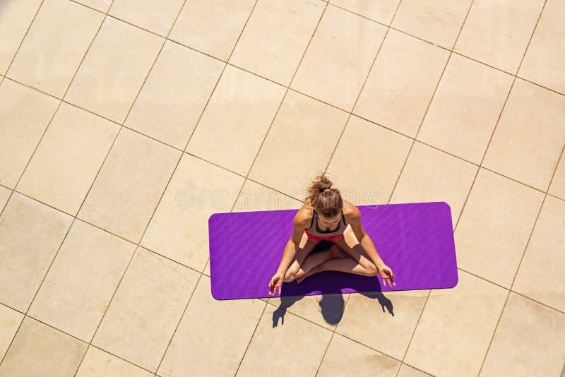 Mujer joven en la posición de loto en el día soleado, al aire libre, visión desde a imagen de archivo libre de regalías
