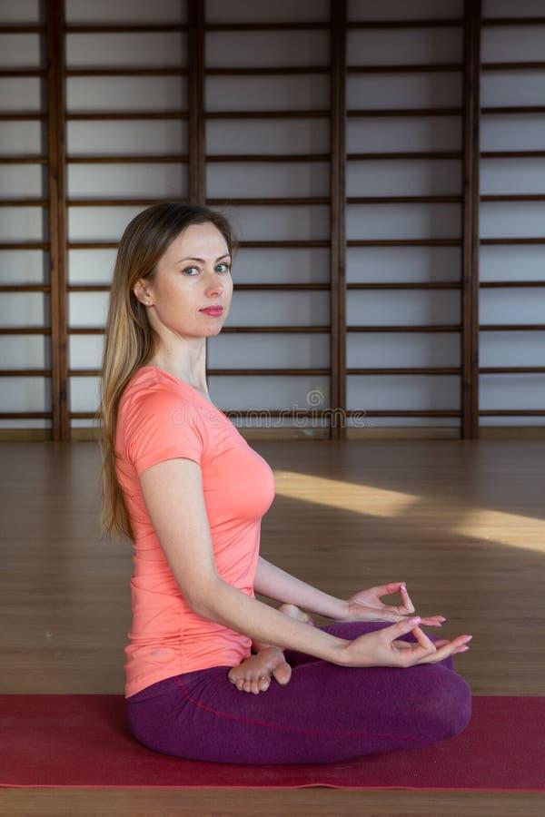 Mujer joven en la posición de loto mientras que medita foto de archivo