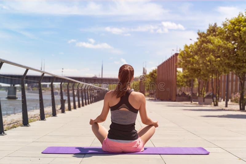 Mujer joven en la posición de loto que hace yoga imagenes de archivo