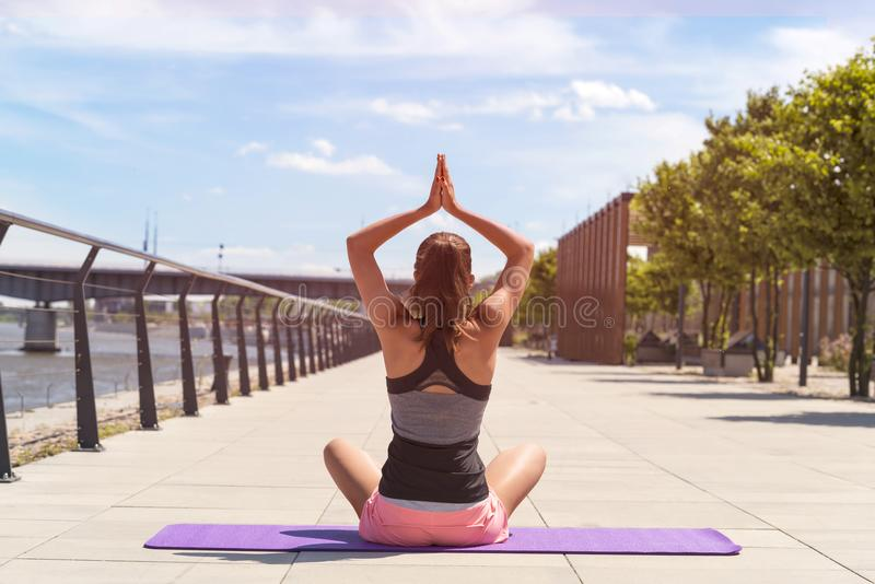 Mujer joven en la posición de loto que hace yoga en la ciudad imágenes de archivo libres de regalías