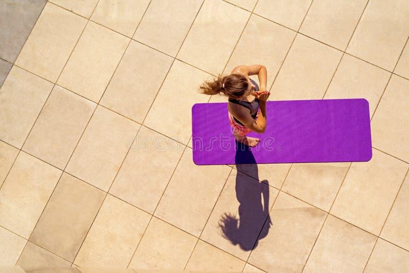 Mujer joven en la posición de la yoga en el día soleado, al aire libre, visión desde el ab fotografía de archivo libre de regalías