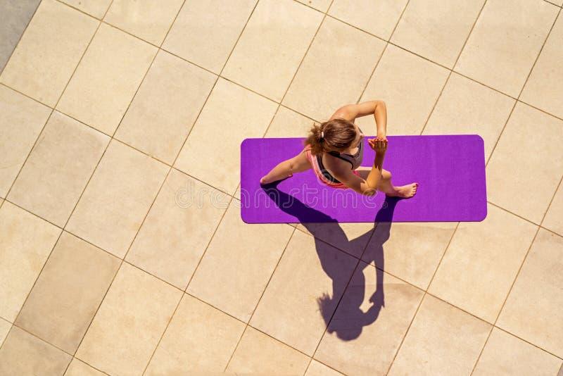 Mujer joven en la posición de la yoga en el día soleado, al aire libre, visión desde el ab fotografía de archivo