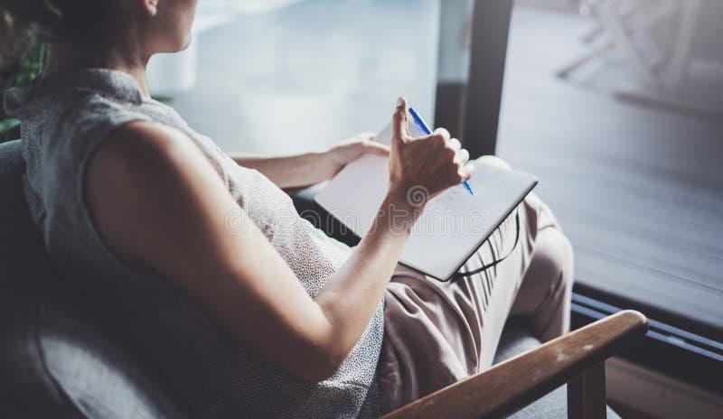 Mujer joven en la ropa casual que se sienta en la tabla en hogar y que escribe en cuaderno Freelancer que trabaja a casa foto de archivo libre de regalías