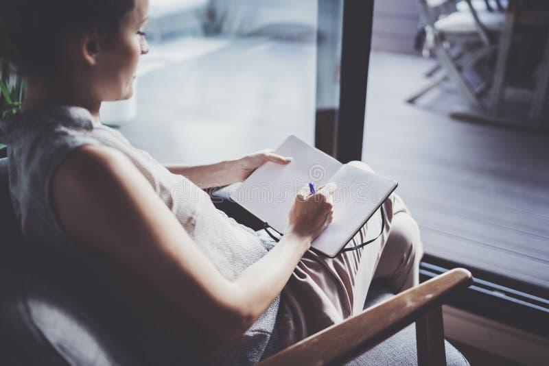 Mujer joven en la ropa casual que se sienta en la tabla en hogar y que escribe en cuaderno Freelancer que trabaja a casa fotos de archivo libres de regalías