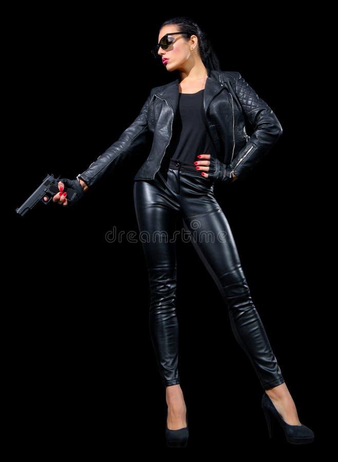 Mujer joven en la ropa de cuero con el arma fotografía de archivo