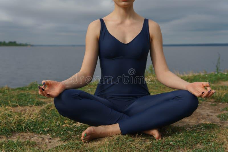 Mujer joven en la ropa de deportes azul que se sienta en actitud de la yoga, cielo nublado y el lago en fondo imagenes de archivo