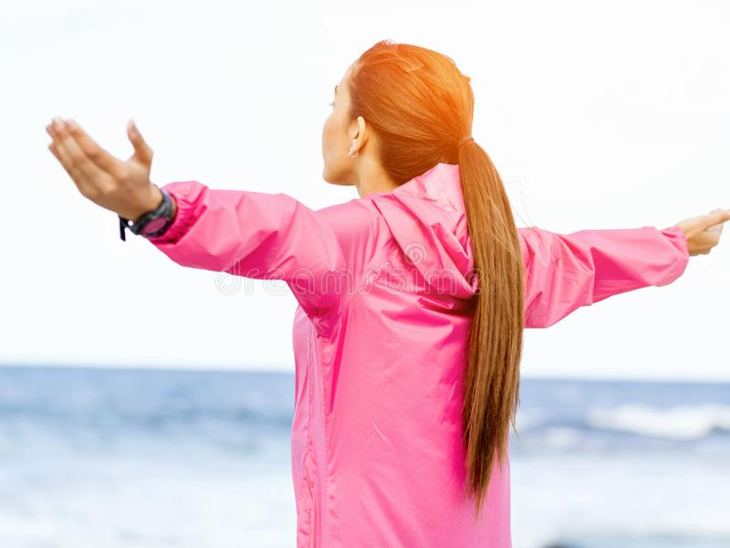 Mujer joven en la ropa de deportes que se coloca en la playa imagen de archivo libre de regalías