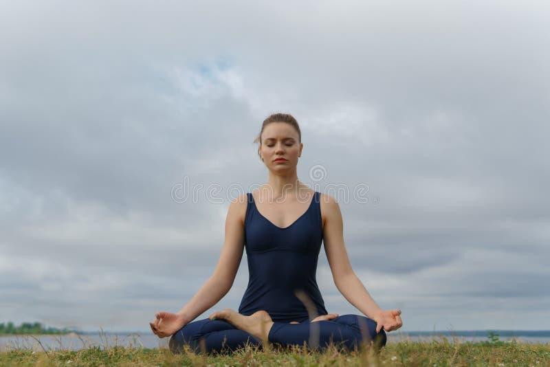 Mujer joven en la ropa de deportes que se sienta en actitud de la yoga fotos de archivo libres de regalías