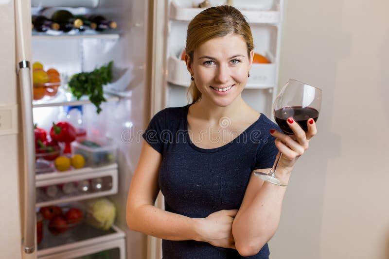 Mujer joven en la ropa de noche que bebe el vino rojo cerca del refrigerador fotografía de archivo