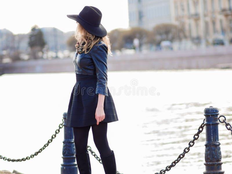 Mujer joven en la ropa elegante contra la perspectiva de la ciudad, retrato romántico Retrato del blonde encantador encendido foto de archivo libre de regalías