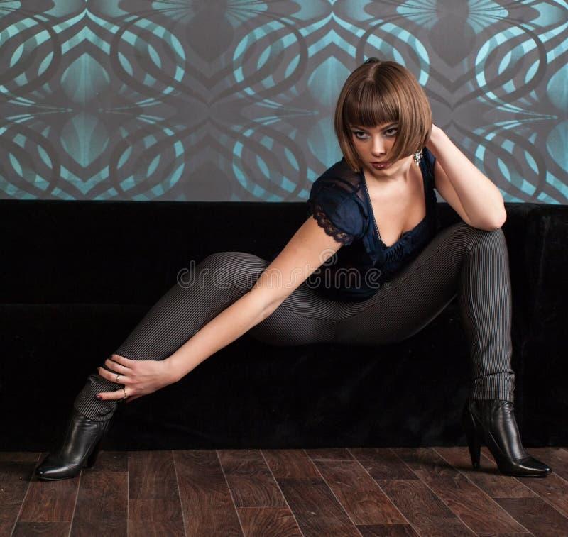 Mujer joven en la ropa oscura que se sienta en el sofá fotos de archivo libres de regalías