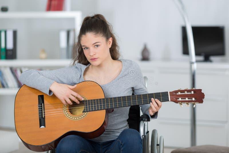 Mujer joven en la silla de ruedas que toca la guitarra fotografía de archivo