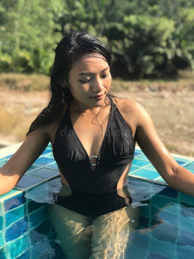 Mujer joven en la situación del traje de baño en piscina azul foto de archivo libre de regalías