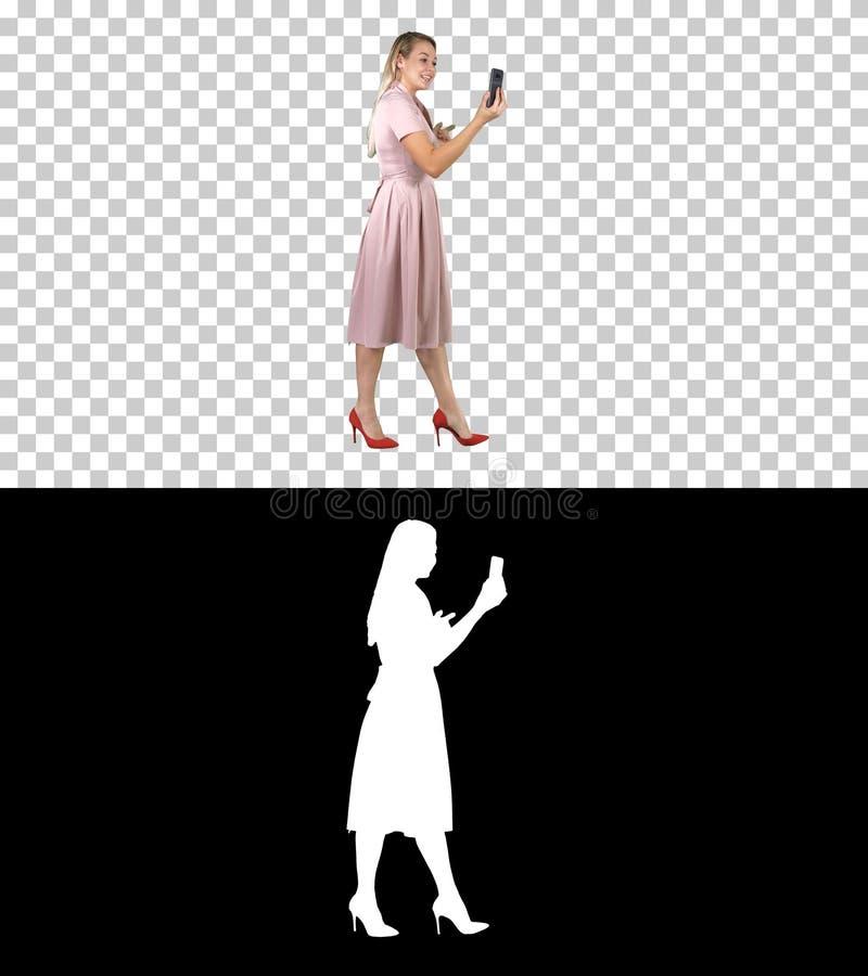 Mujer joven en la tenencia rosada usando blog video de registraci?n del tel?fono elegante mientras que camina, Alpha Channel imagenes de archivo