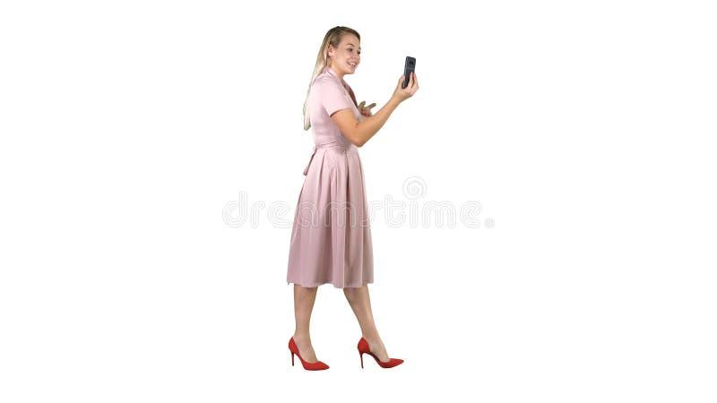 Mujer joven en la tenencia rosada usando blog video de registración del teléfono elegante mientras que camina en el fondo blanco imagenes de archivo