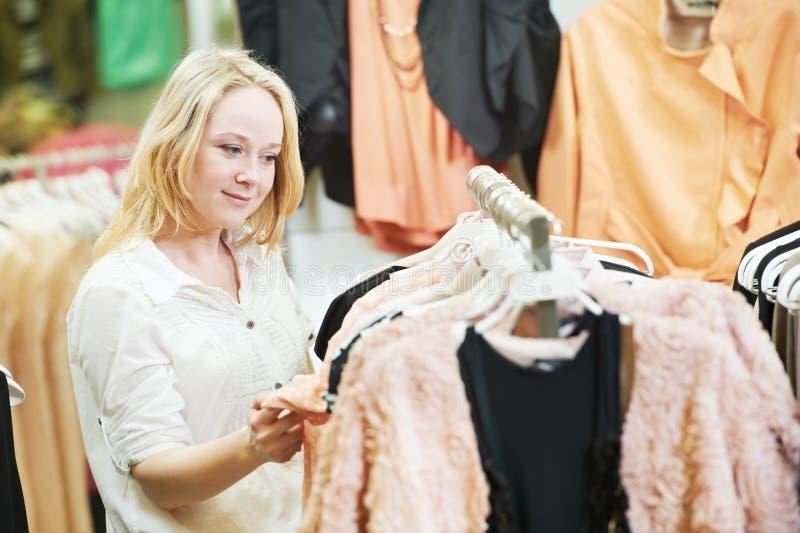 Mujer joven en la tienda que hace compras de la ropa imagenes de archivo