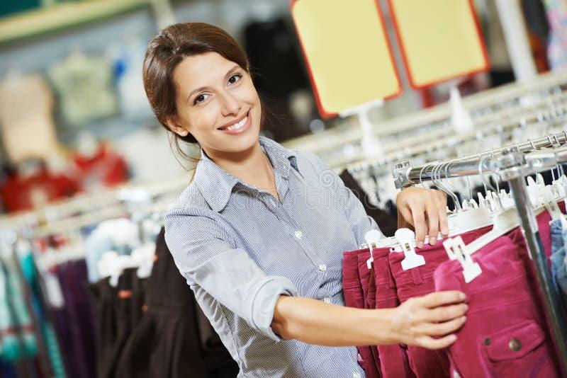 Mujer joven en la tienda que hace compras de la ropa imagen de archivo