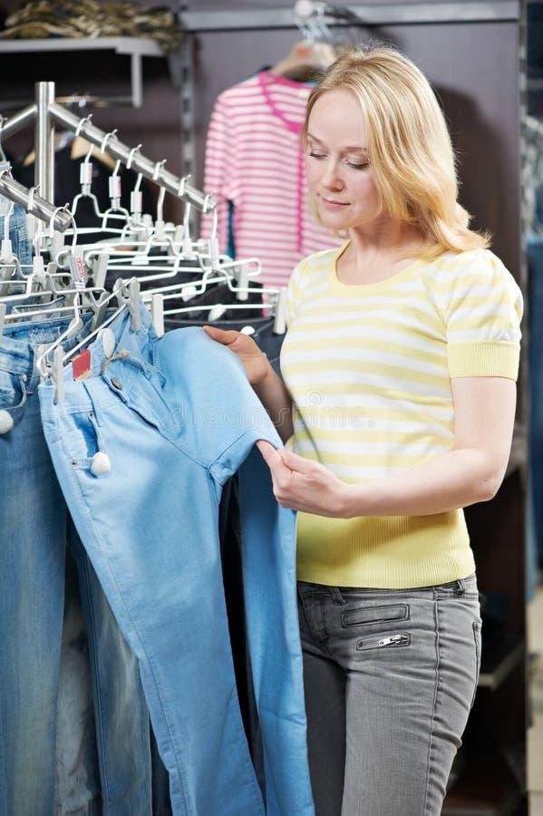 Mujer joven en la tienda que hace compras de la ropa imágenes de archivo libres de regalías