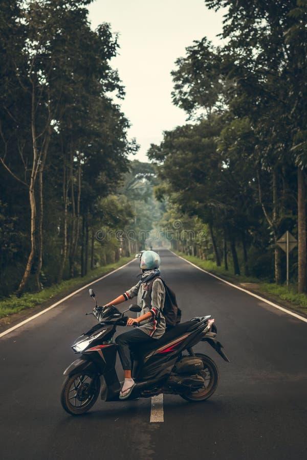 Mujer joven en la vespa en el camino entre los árboles Isla de Bali foto de archivo