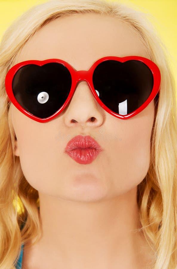 Mujer joven en las gafas de sol que soplan beso de los labios fotografía de archivo