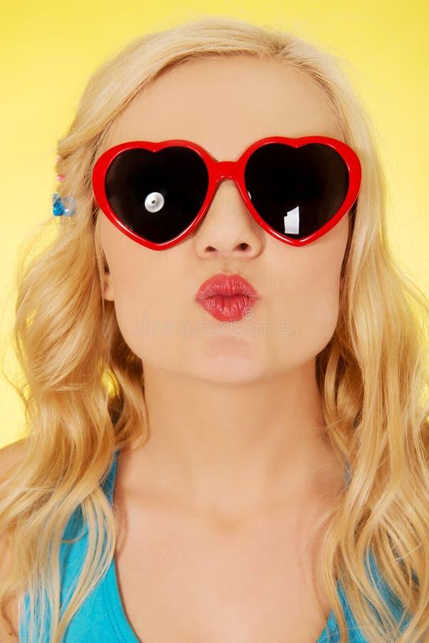 Mujer joven en las gafas de sol que soplan beso de los labios foto de archivo