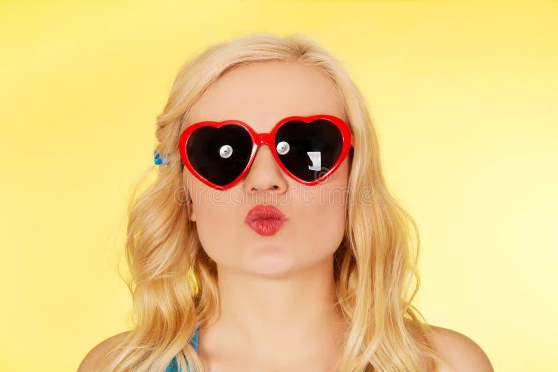 Mujer joven en las gafas de sol que soplan beso de los labios imagenes de archivo