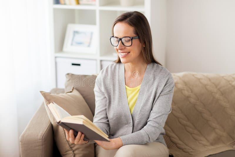 Mujer joven en libro de lectura de los vidrios en casa foto de archivo