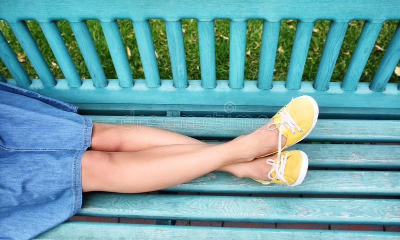 Mujer joven en los gumshoes que descansan sobre banco al aire libre imagenes de archivo