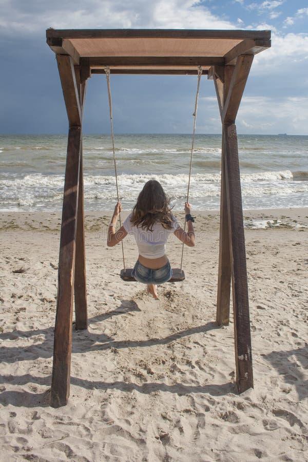 Mujer joven en los pantalones cortos del dril de algodón y la camiseta blanca que balancean en un oscilación por el mar imagen de archivo
