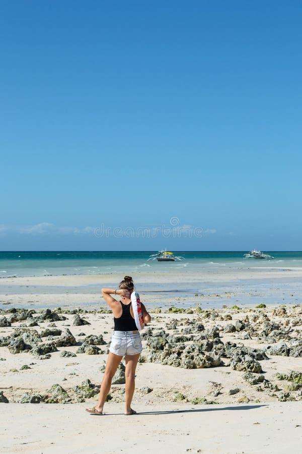 Mujer joven en los pantalones cortos que hacen una pausa el mar imagen de archivo libre de regalías