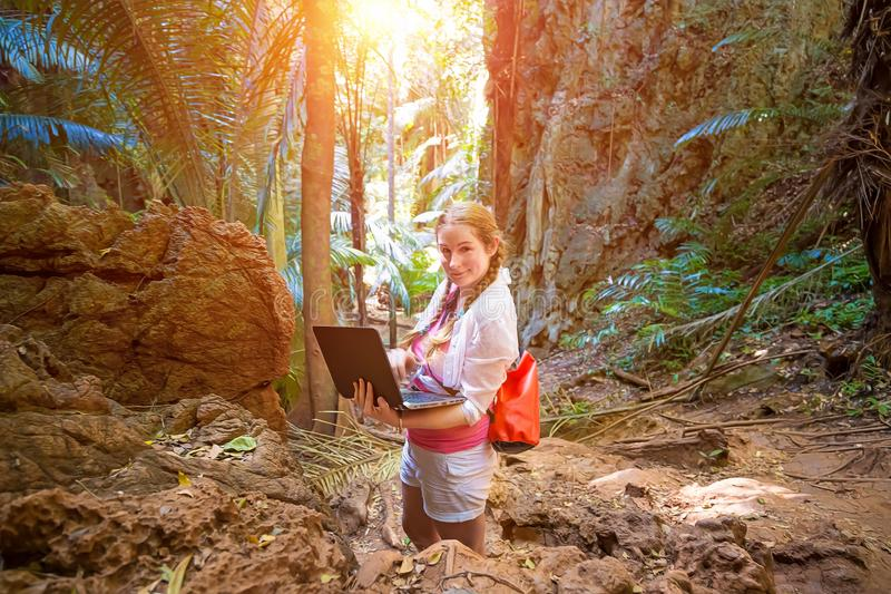 Mujer joven en los trabajos blancos con un ordenador portátil en las montañas y la selva tropical Trabajo en viaje ?l mira en la  imagen de archivo