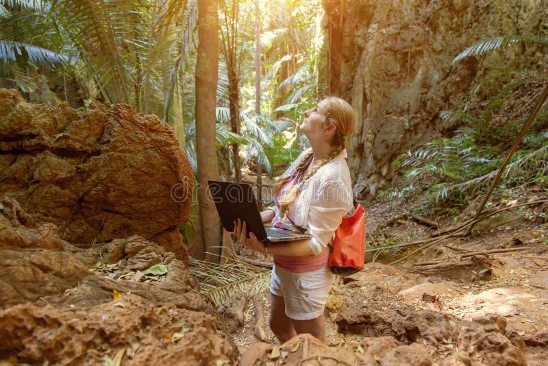 Mujer joven en los trabajos blancos con un ordenador port?til en las monta?as y la selva tropical Trabajo en viaje Él mira para a fotografía de archivo libre de regalías