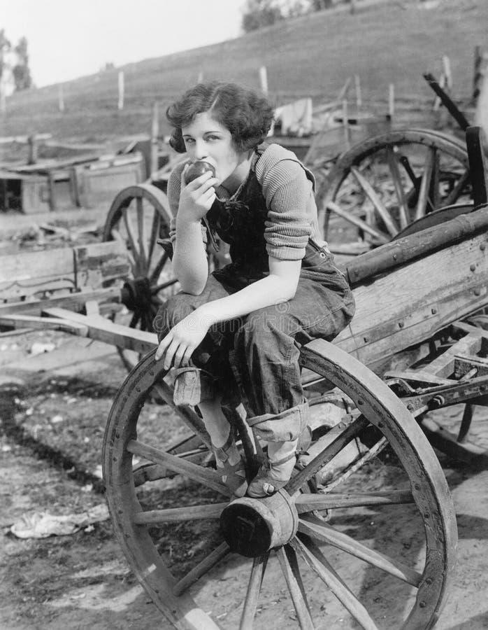 Mujer joven en los vaqueros de trabajo que se sientan en la rueda que come una manzana (todas las personas representadas no son v fotos de archivo