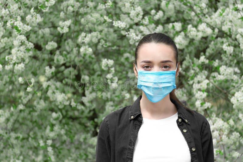 Mujer joven en máscara protectora cerca del árbol floreciente Concepto de la alergia fotografía de archivo