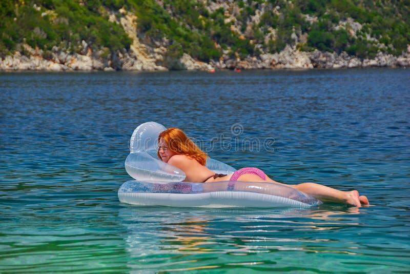 Mujer joven en Matress inflable en el mar imagenes de archivo