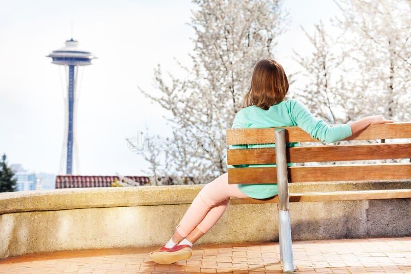 Mujer joven en mirada del banco en la aguja del espacio fotos de archivo libres de regalías
