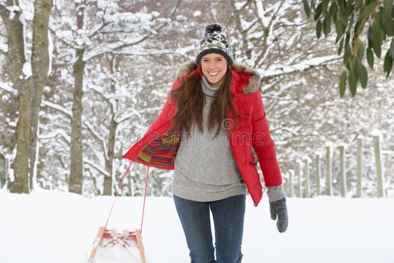 Mujer joven en nieve con el trineo foto de archivo