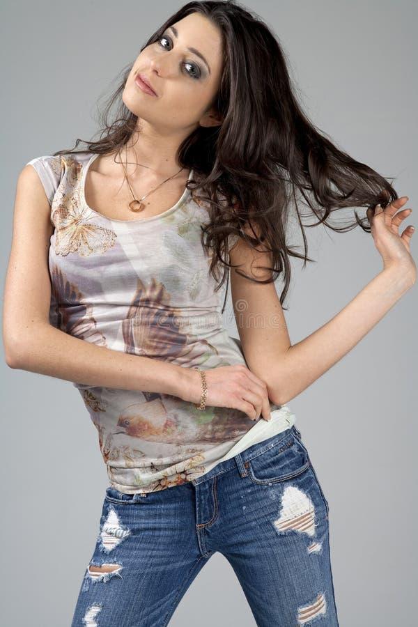 Mujer joven en pantalones vaqueros y la camisa blanca foto de archivo