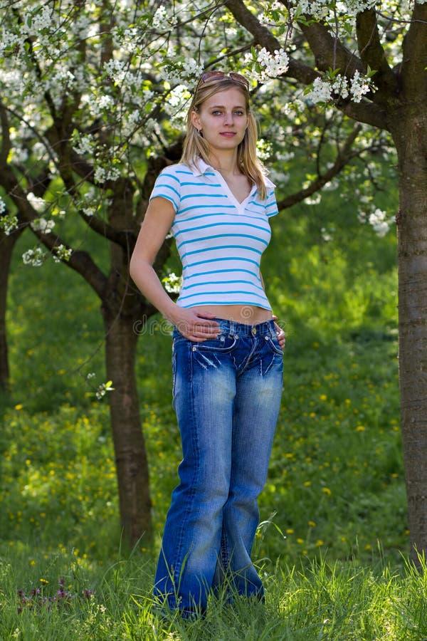 Mujer joven en parque floreciente foto de archivo