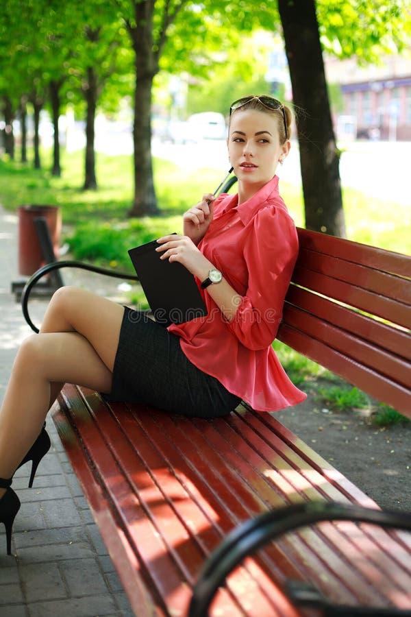 Mujer joven en parque verde, con la libreta y la pluma imágenes de archivo libres de regalías