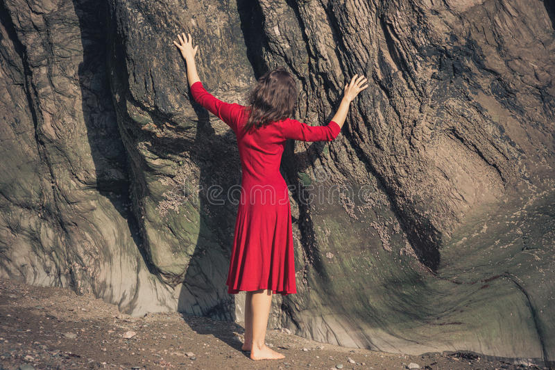 Mujer joven en roca conmovedora del vestido rojo fotografía de archivo libre de regalías