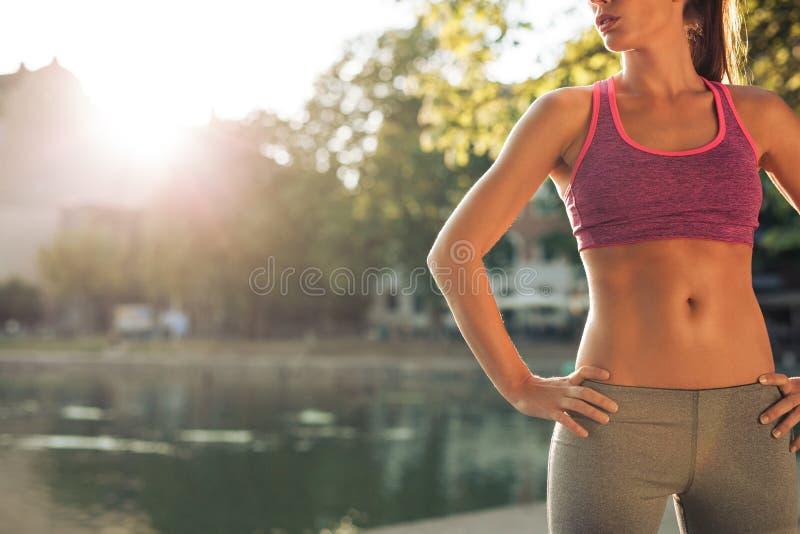 Mujer joven en ropa de deportes con el cuerpo del ajuste imagen de archivo libre de regalías