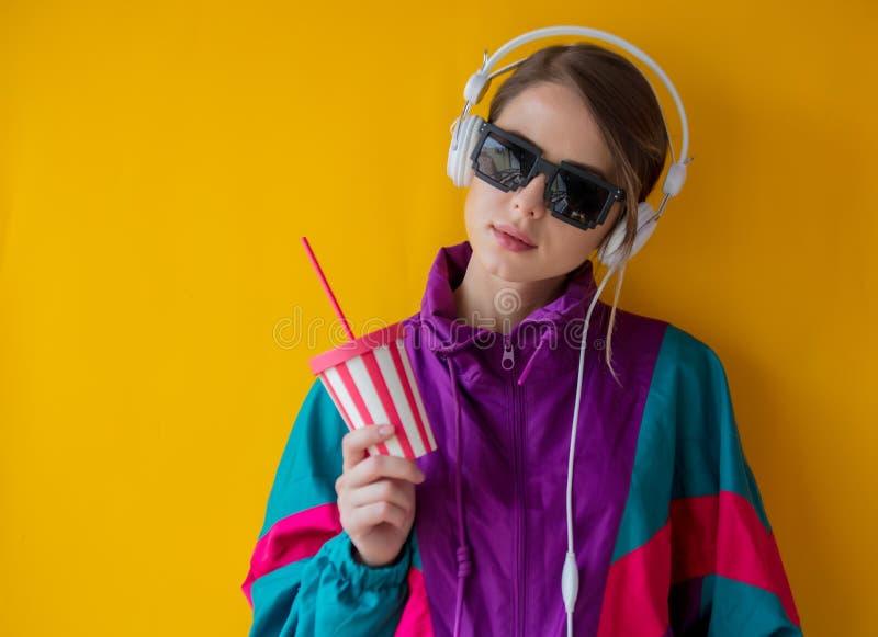 Mujer joven en ropa del estilo 90s con la taza y los auriculares imagenes de archivo