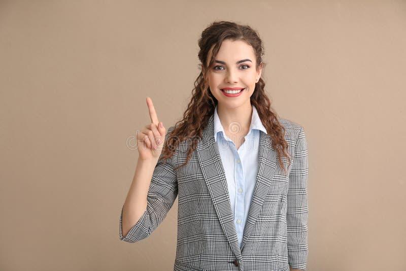 Mujer joven en ropa formal con el dedo índice aumentado en fondo del color imágenes de archivo libres de regalías