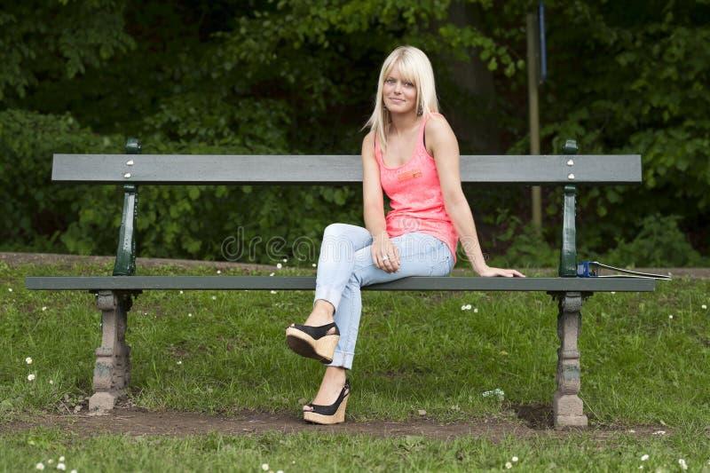 Mujer joven en rosa asentada en un banco al aire libre fotos de archivo libres de regalías