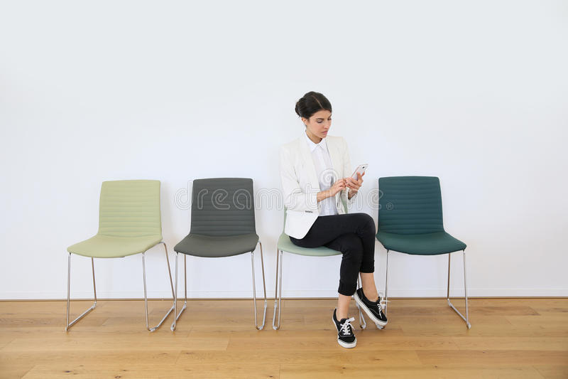 Mujer joven en sala de espera usando smartphone imágenes de archivo libres de regalías